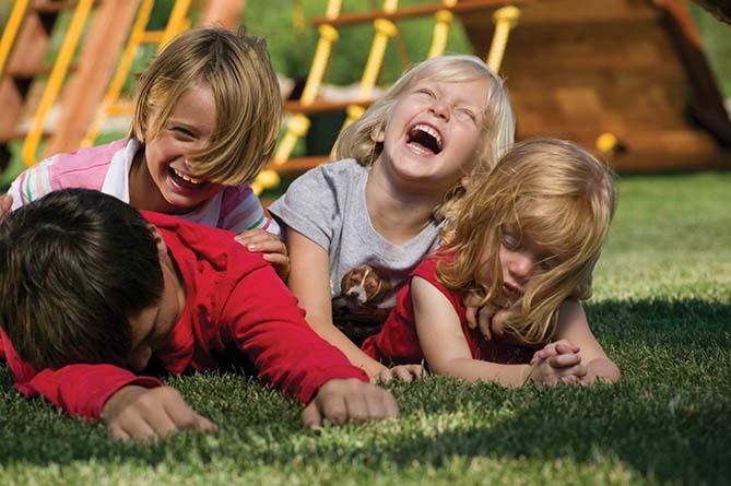 Дети смеются в траве возле Rainbow