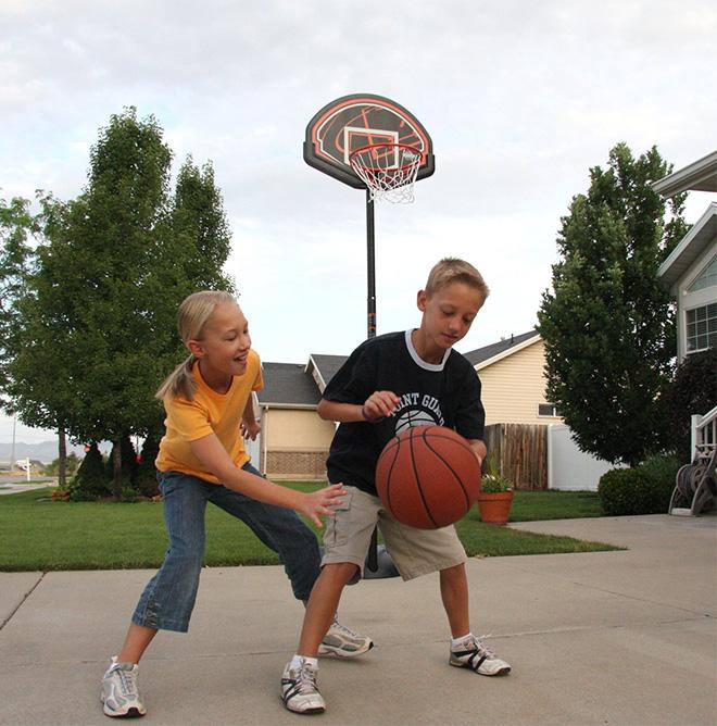 Брат и сестра играют в баскетбол во дворе